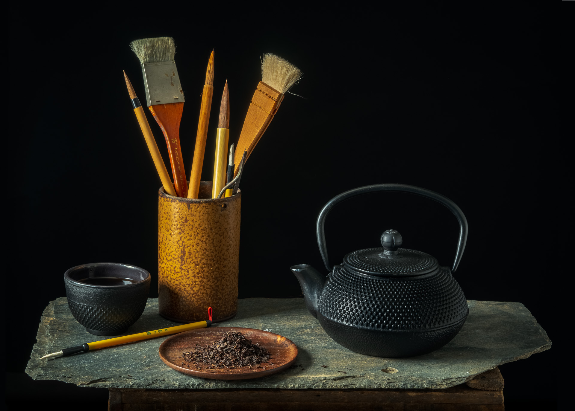 A Japanese Tea Pot and Cup with tea leaves and calligraphy brushed and vase